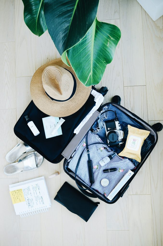 An open suitcase with a camera, hat, and beauty products