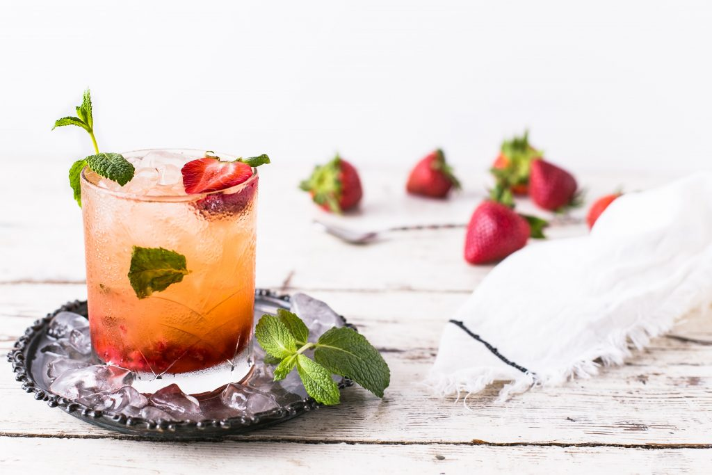 A cold summer cocktail with strawberries and mint